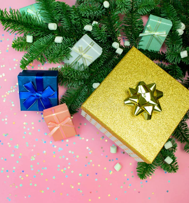 Flat lay gift box with ribbon, marshmallow, christmas fir tree and rainbow holographic stars confetti. Holiday square social media. Pink, mint, blue, gold gift royalty free stock photos