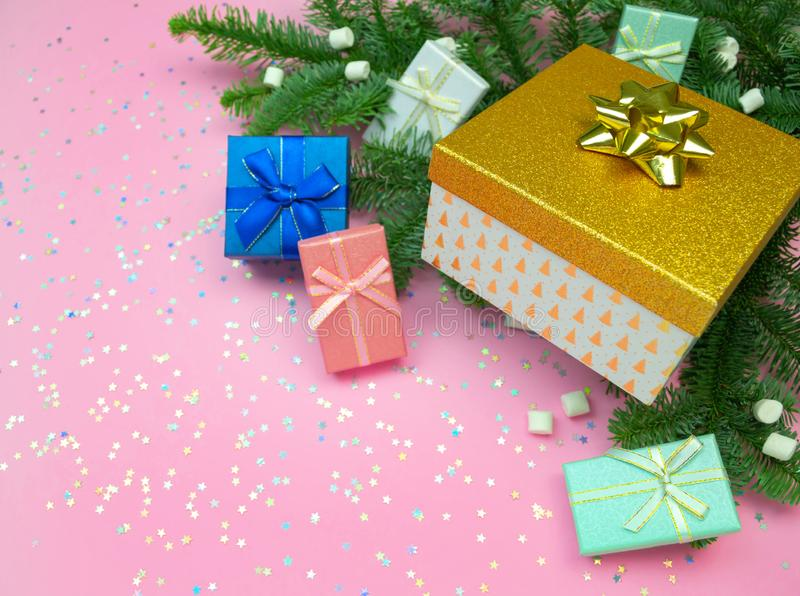 Pink, mint, blue, gold gift box with ribbon, marshmallow, christmas tree branches and rainbow holographic stars confetti. Flat lay on pink background. Top view royalty free stock images