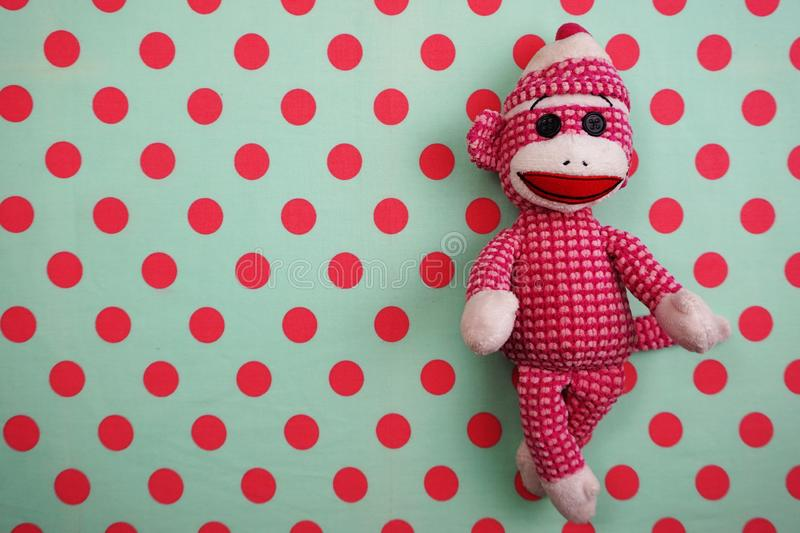 Pink Monkey Doll Top view on Pink and green Polka dot background royalty free stock photos