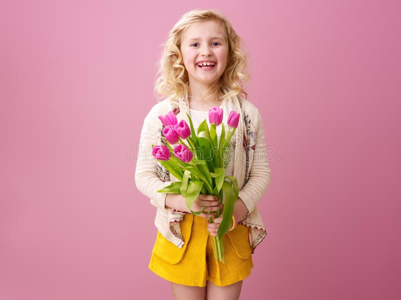 Happy modern girl isolated on pink with bouquet of tulips stock photography