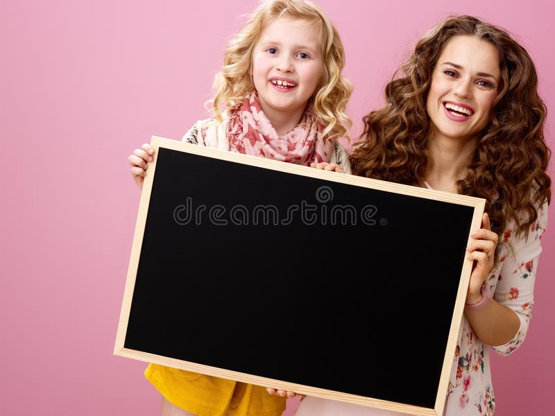 Mother and daughter on pink background showing blank board royalty free stock photo