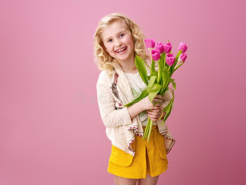 Smiling modern girl on pink background with bouquet of flowers royalty free stock photography