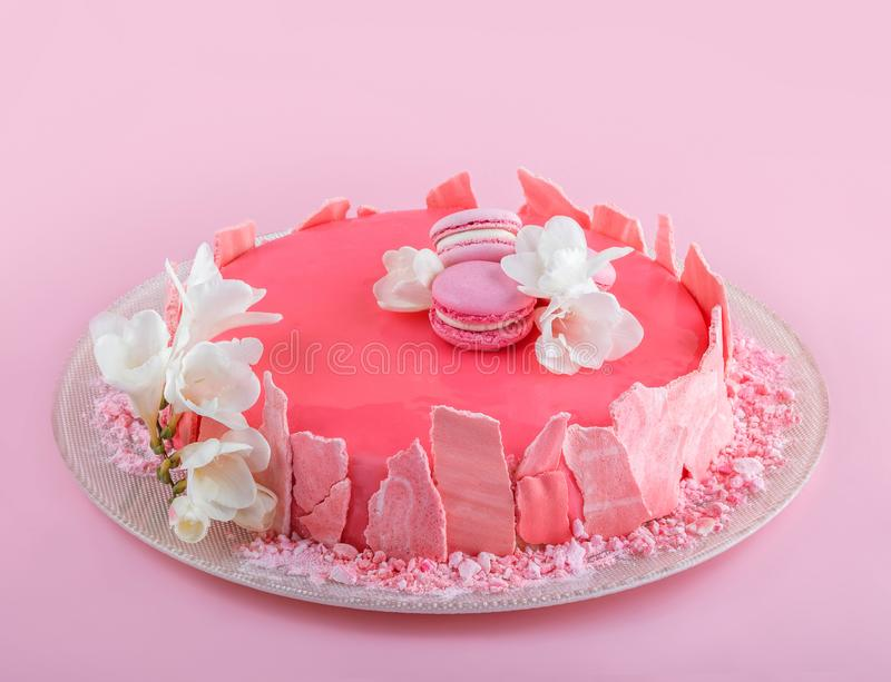 Pink mousse cake with mirror glaze decorated with macaroons, flowers for Happy Birthday on pink holiday background. Holiday cake royalty free stock photography