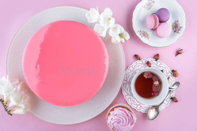 Pink mousse cake with mirror glaze decorated with macaroons, flowers for Happy Birthday on pink holiday background. Holiday cake royalty free stock photos