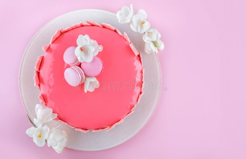Pink mousse cake with mirror glaze decorated with macaroons, flowers for Happy Birthday on pink holiday background stock images