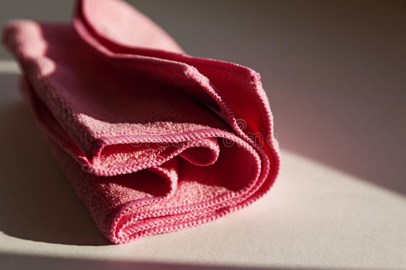 A pink nonwoven cloth lying in the windowsill stock image