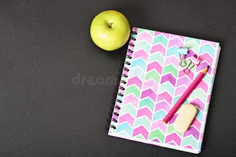 Pink notebook and apple on black background. Top view of girly pink notebook with pencil, eraser, binder clips and apple on black background stock photos