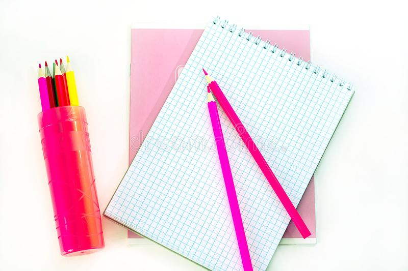 Pink notebook, opened notepad and pencils on a white background. Back to school, education concept, fashion office stock photography