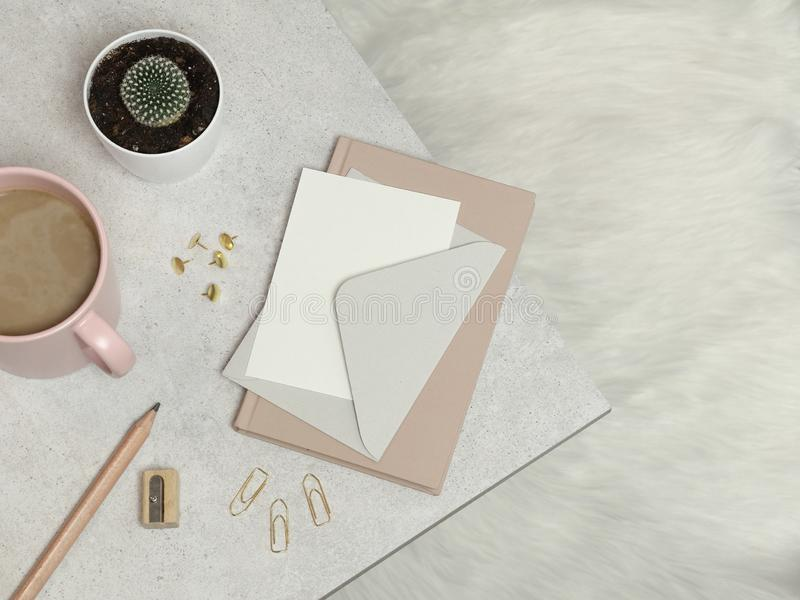 The notebook, silver envelope, pencil, sharpener, paper clips, pins,  cup of coffee, cactus,  on the granite table and white stock image