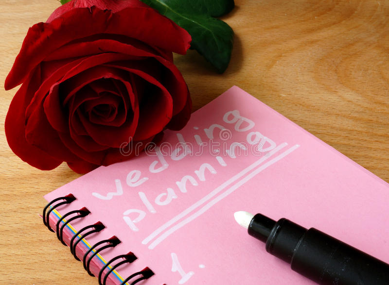 Pink notepad with wedding planning and rose. stock image