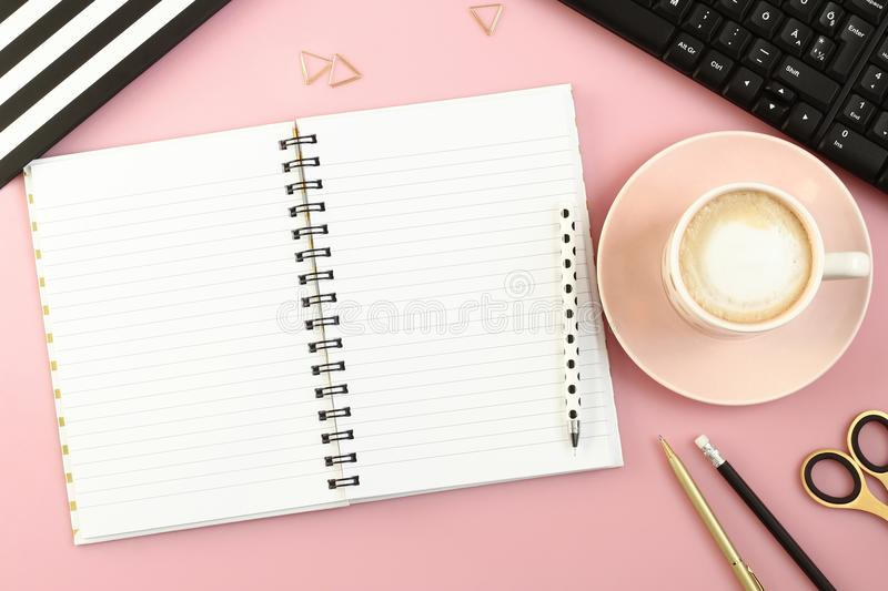 Pink office desk table with open notebook, cup of coffee, pen, pencil, scissors and computer. royalty free stock photography