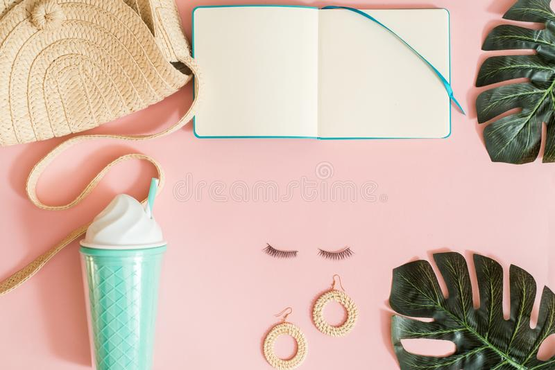 Pink office table with cup of coffee, flowers, macarons, pen, pencil, make up brush, notebook and empty paper. Woman`s accessorie royalty free stock photo
