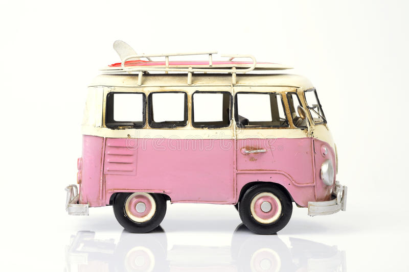 Pink old toy car with surfboard. Old toy car in pink with surfboard on the roof on white background stock photo