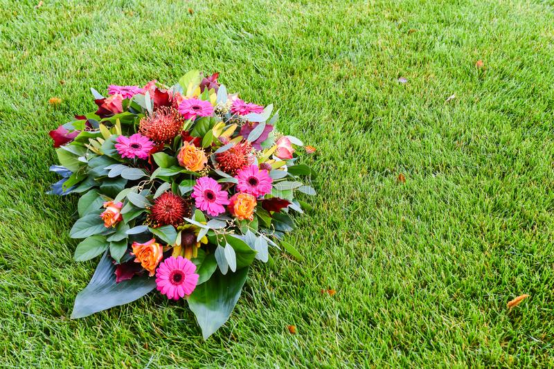 Pink and orange colored flower arrangement on lawn. All Saints day flower arrangements, flowers for grave and funeral. stock image