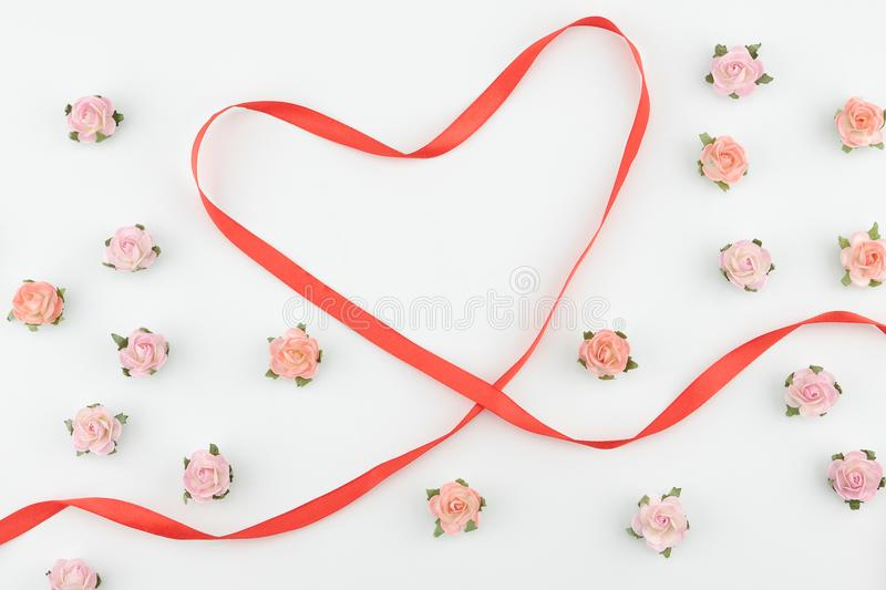 Pink and orange paper flowers with red heart ribbon stock images