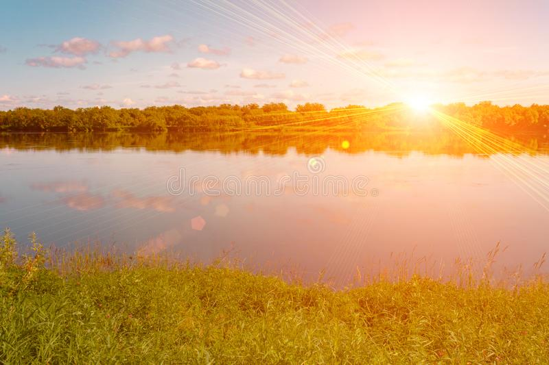 Pink orange summer evening sky. Sun rays and clouds reflecting in water. Meadow and forest on banks royalty free stock photos