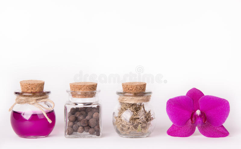 Pink orchid and three glass bottles on a white background. Spa concept. Cosmetic bottles. Ecological natural cosmetics. Copy space stock photo