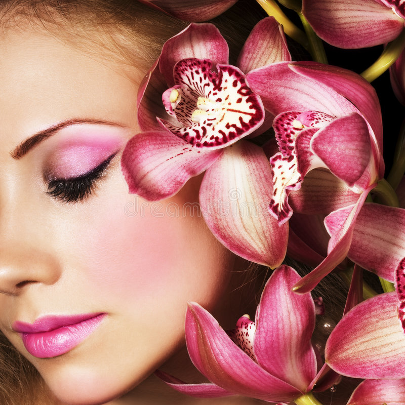 Pink Orchids. Woman with beautiful makeup and pink orchids