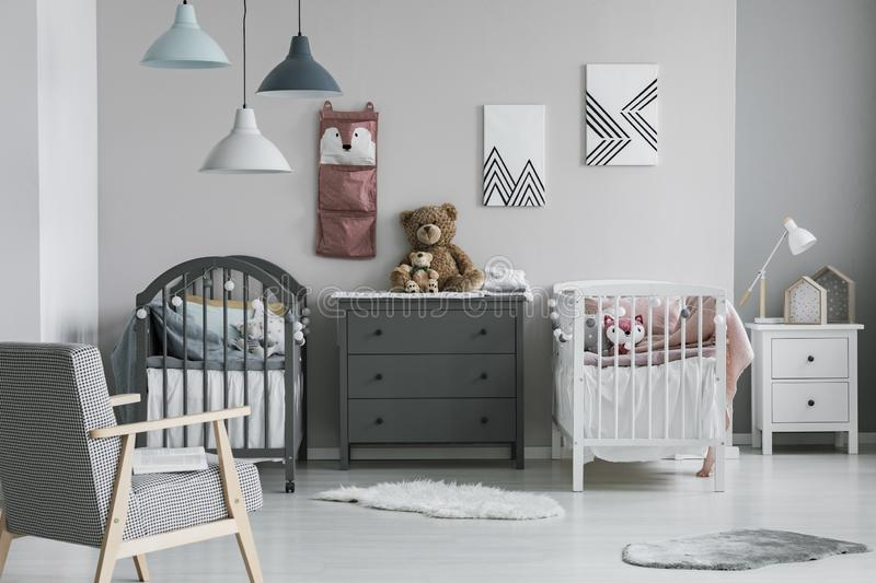 Pink organizer on wall of trendy baby bedroom with two cribs and chest of drawers stock images