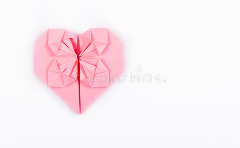Pink origami heart on a white background. A valentine made of paper. royalty free stock photos