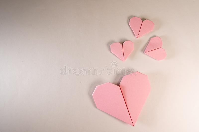 Pink origami hearts on a paper background stock photography