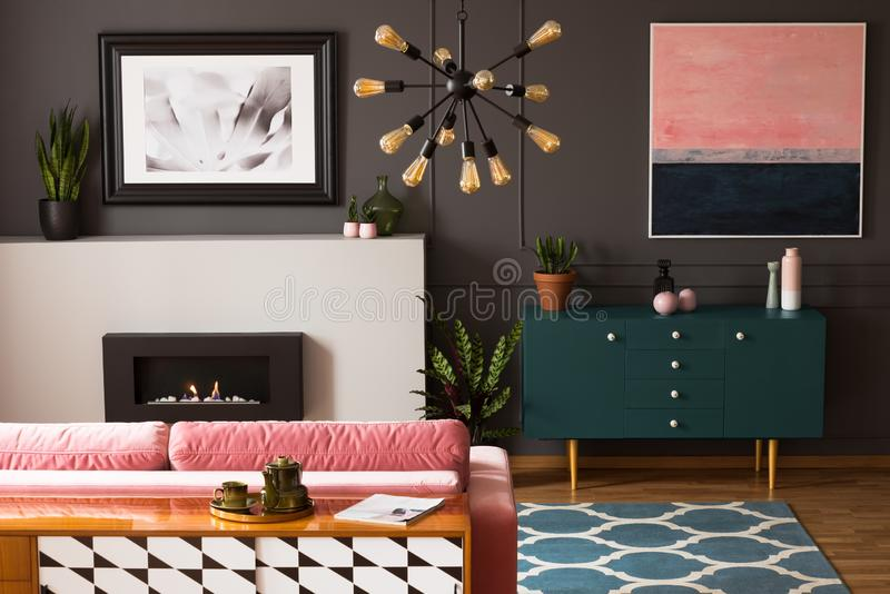 Pink painting above green cabinet in grey flat interior with fireplace in front of couch. Real photo stock photography