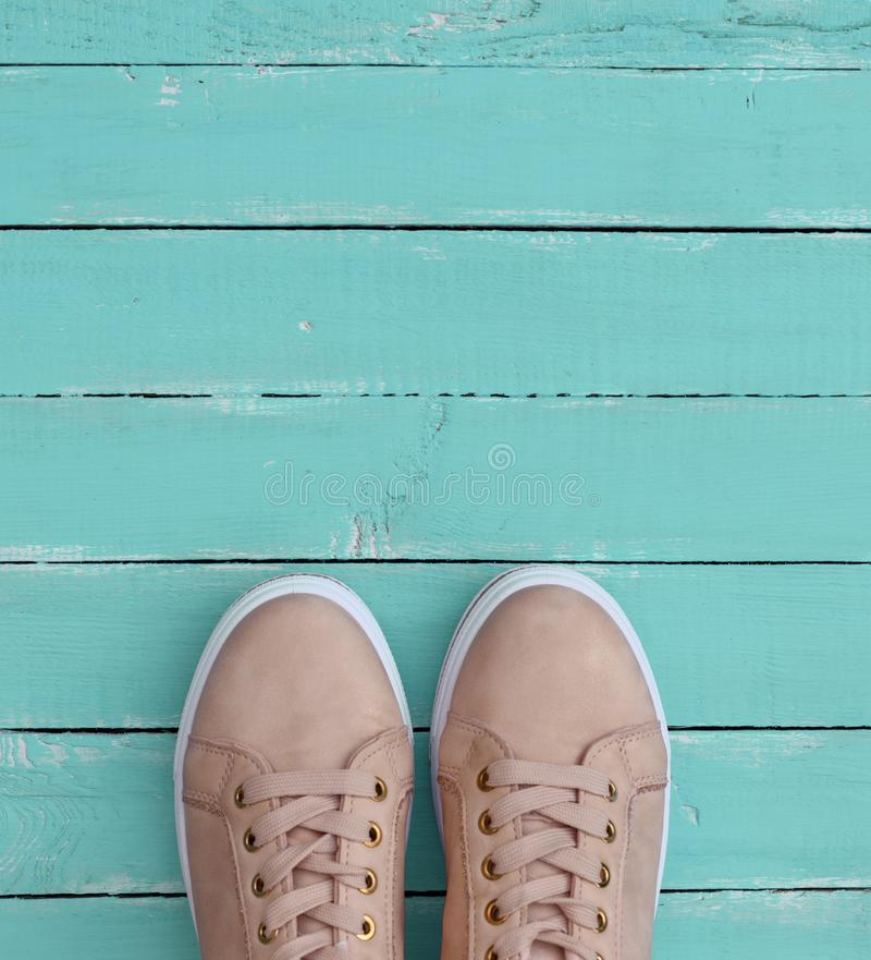 Pink pair of female leather sneakers with laces. On a blue wooden background royalty free stock photo