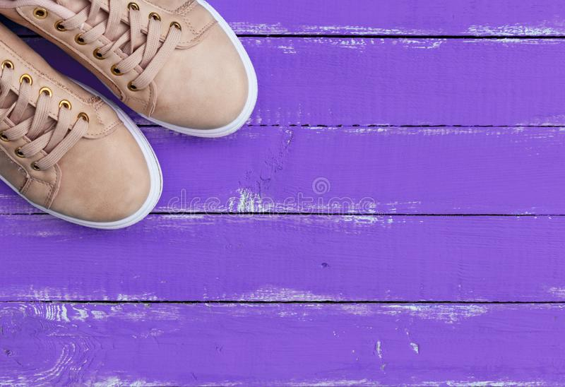 Pink pair of female leather sneakers with laces. Top view of a pink pair of female leather sneakers with laces on a purple wooden background royalty free stock photo
