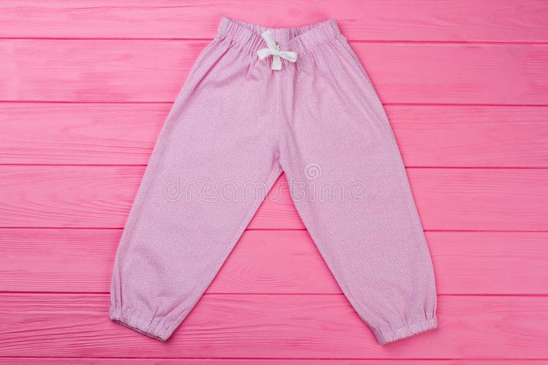 Pink pants with fine pattern. Pajama`s bottom with elastic cuffs and waist. Cute garments for toddler girls stock photos