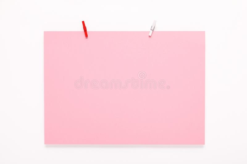 Paper card on clothes peg on white background. Pink paper card on a clothes peg on a white background royalty free stock image