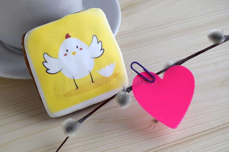 Pink paper in the form of heart attached by office paper clip to a branch of a willow and gingerbread with the image of chicken is. Pink paper in the form of stock images