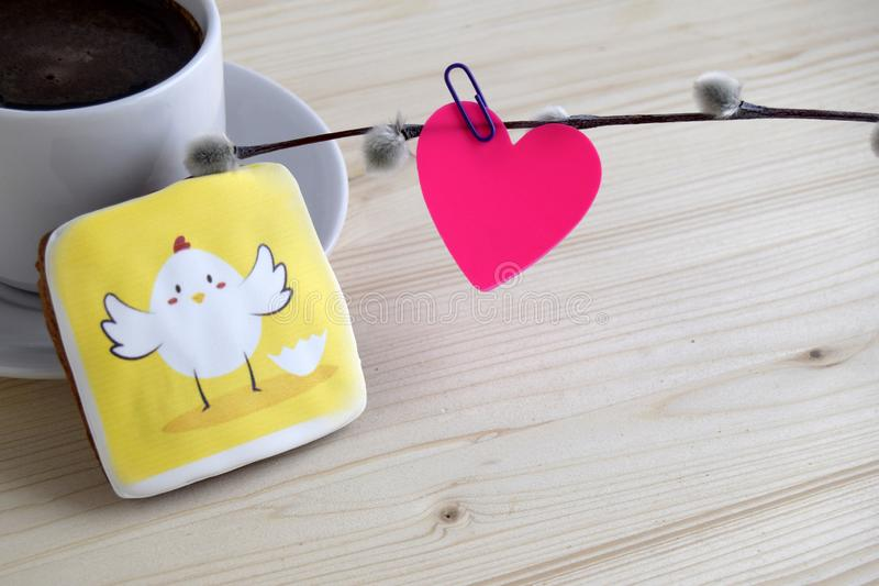 Pink paper in the form of heart is attached by office paper clip to a willow branch, gingerbread with the image of chicken and a. Pink paper in the form of heart royalty free stock image