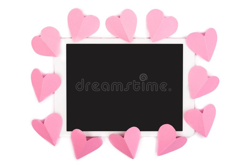 Pink paper hearts framing touchpad with blank screen isolated on white stock images