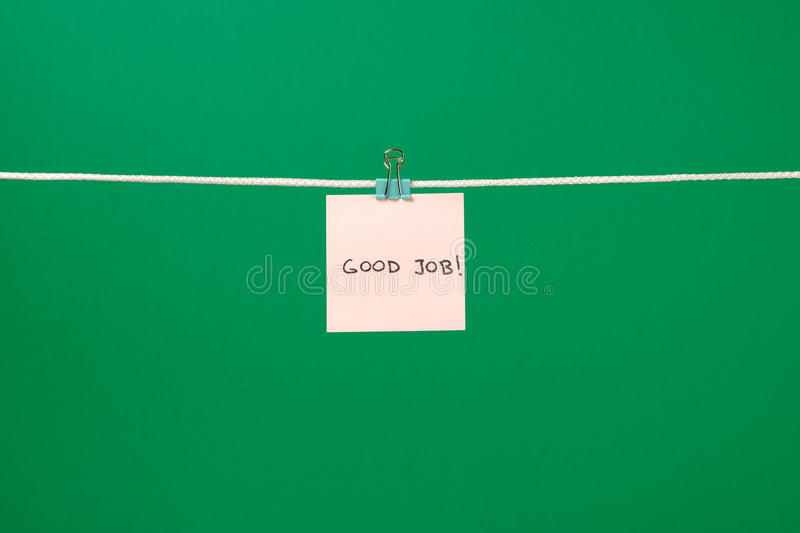 Pink paper sheet on the string with text Good Job. Over colorful background royalty free stock image