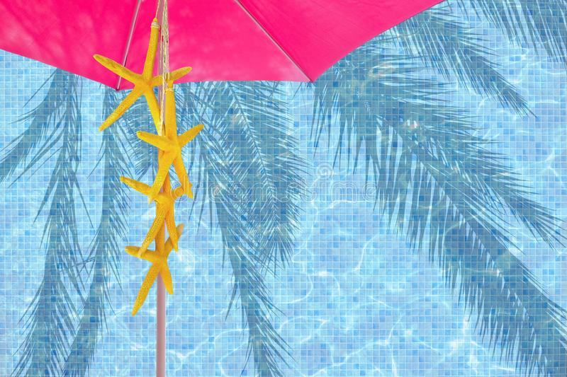Pink parasol yellow starfish turquoise blue pool. Water surface background stock image