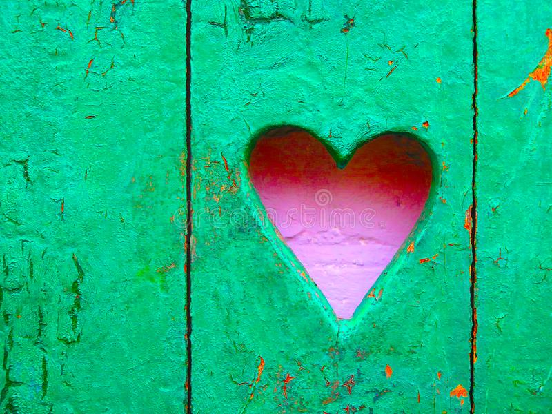 Pink pastel heart on green wooden rustic wall stock photos