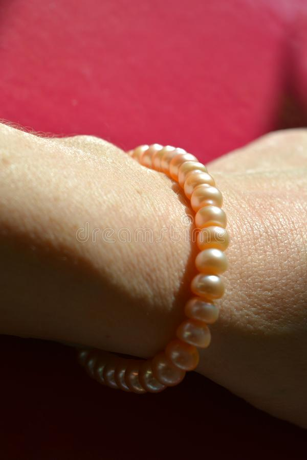 Pink pearls bracelet on the female hand pink background stock photo
