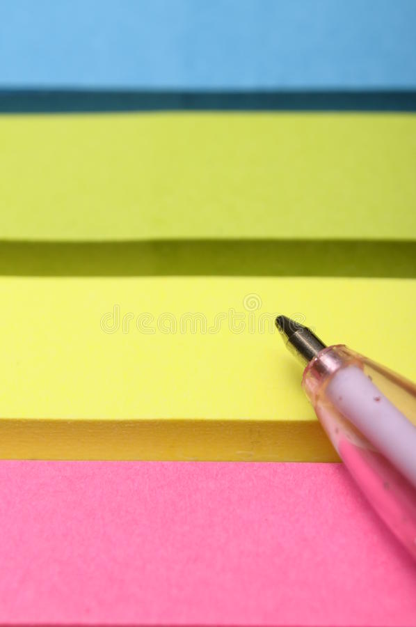 Pink Pen And Colored Pieces Of Paper Royalty Free Stock Photos