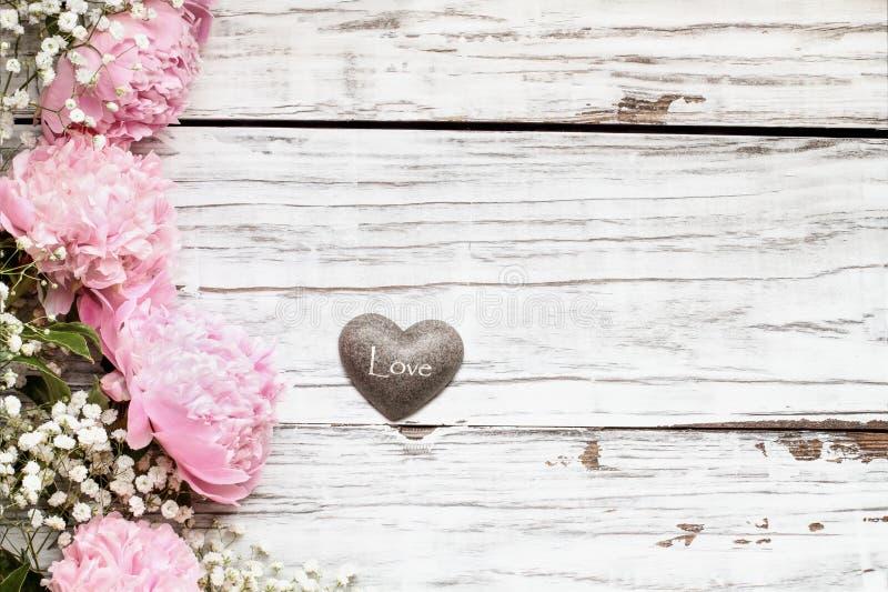 Pink Peonies Babys Atemblumen und Herz über einem rustikalen Hintergrund aus weißem Holz stockfotos
