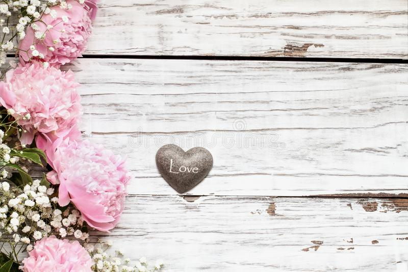 Pink Peonies Babys Breath Flowers and Heart over een Rustige White Wood Background stock foto's