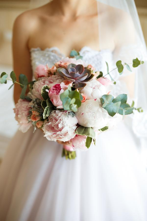 Pink peony wedding bouquet in bride`s hands royalty free stock images