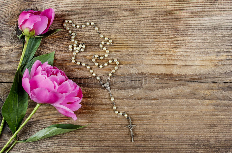 Pink peony and white rosary. On wooden background. Rough surface, copy space royalty free stock photos