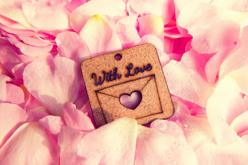 Pink petals with droplets and wooden heart shape with love text royalty free stock photos