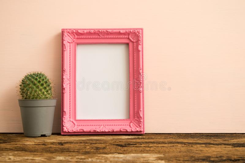 Pink photo frame on old wooden table with cactus over pink wall royalty free stock image