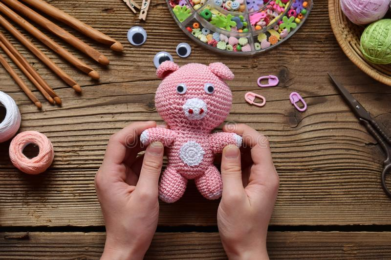 Pink pig. Crochet toy for child. On table threads, needles, hook, cotton yarn. Handmade crafts. DIY concept. Small business. royalty free stock image