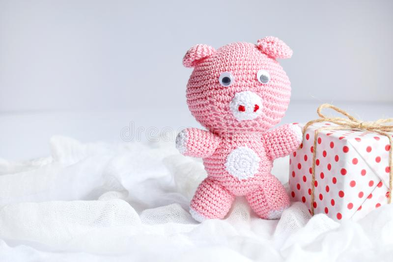 Pink pig, symbol of 2019 and gift on white background. Happy New Year and Merry Christmas card. Crochet toy for child. Handmade. Crafts on holiday with your own stock images