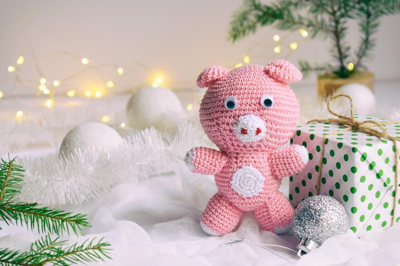 Pink pig, symbol of 2019 and gift on white background. Happy New Year and Merry Christmas card. Crochet toy for child. Handmade stock images