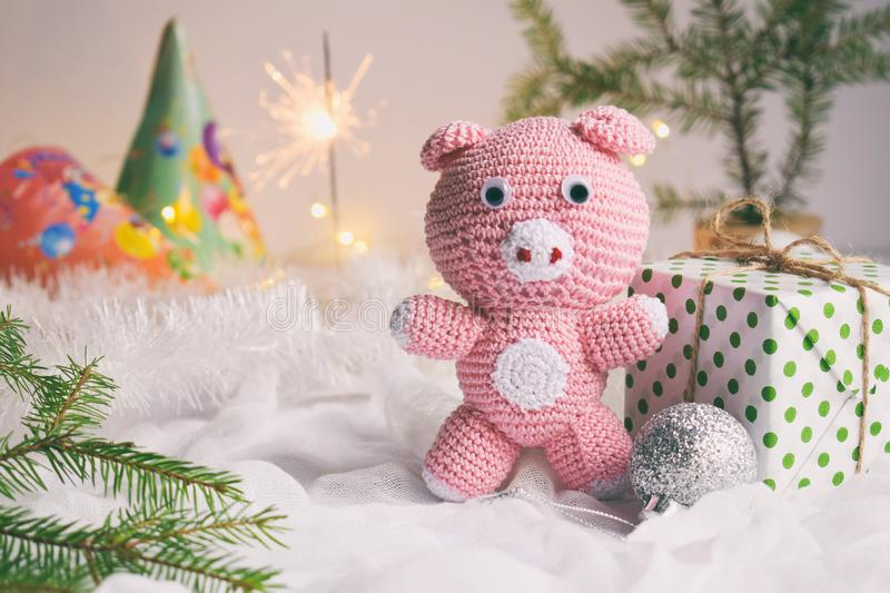 Pink pig, symbol of 2019 and gift on white background. Happy New Year and Merry Christmas card. Crochet toy for child. Handmade royalty free stock photography