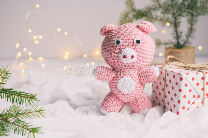 Pink pig, symbol of 2019 and gift on white background. Happy New Year and Merry Christmas card. Crochet toy for child. Handmade royalty free stock image