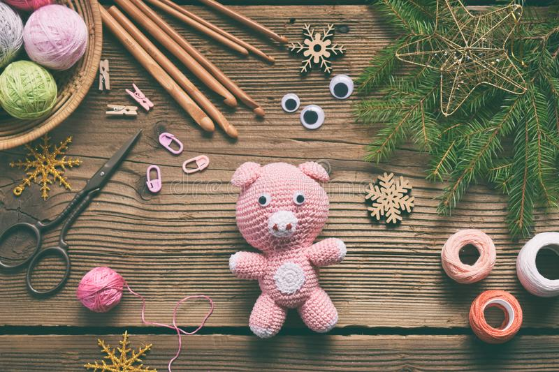 Pink pig, symbol of 2019. Happy New Year. Crochet toy for child. On table threads, needles, hook, cotton yarn. Handmade crafts on stock image